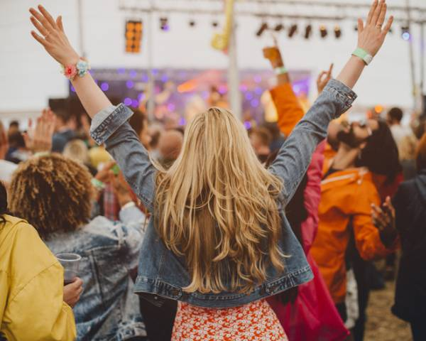 blonde woman at outdoor concert with hands in air