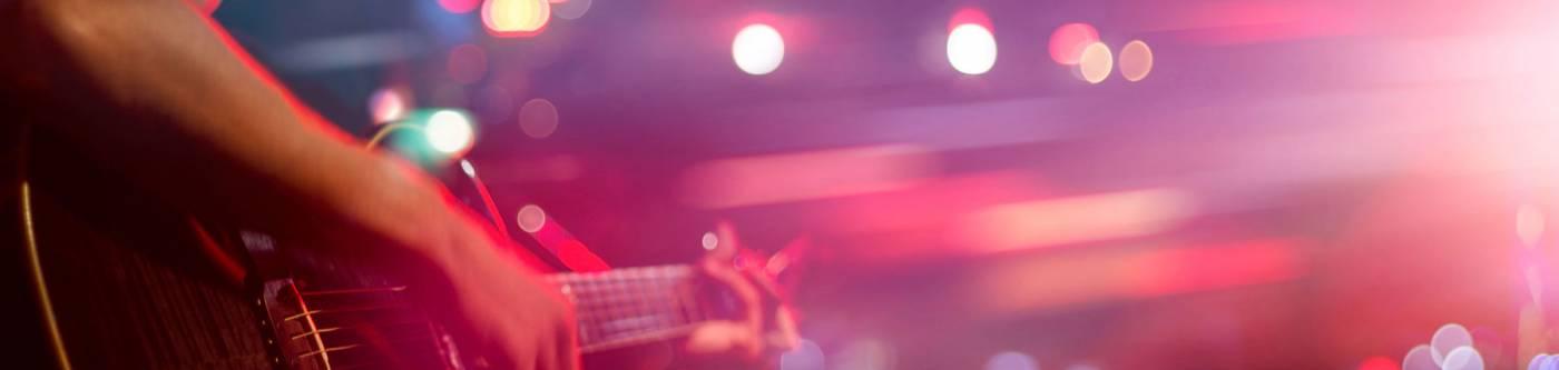 upclose of man's arm playing a guitar